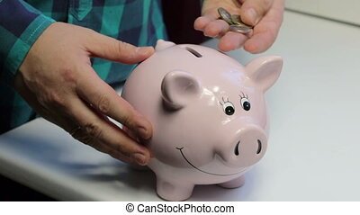 On the table there is a piggy bank in the form of a pink pig. The man in the hands of the coin, which he puts in turn in a piggy bank.