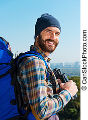 On the top. Handsome young man carrying backpack and looking at camera through the shoulders with smile while standing in the nature and holding binoculars