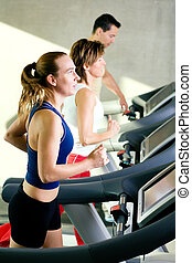 On the treadmill in a gym - Three people on the treadmill in...