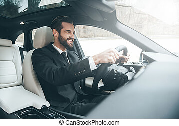 On the way to success. Confident young businessman sitting on the front seat and smiling while driving a car