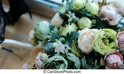 On the windowsill is a bouquet of different roses in pastel colors.
