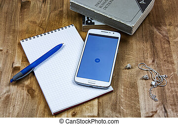 On the wooden surface are books, a notebook with a pen, a smartphone, a chain and earrings