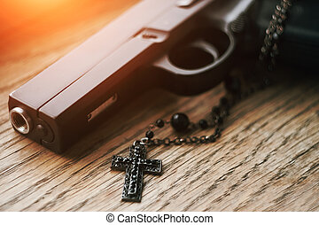 On the wooden surface is a gun and a rosary with a black cross on a chain