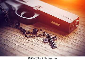 On the wooden surface lies a black gun and a black cross on a chain