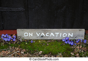 On vacation sign by blue flowers