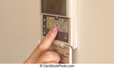 On-wall air conditioner remote control, adjust temperature in room. Close-up