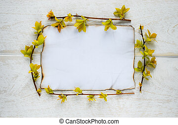 On white wooden boards, a sheet of paper is burned at the edges, and the branches are with yellow leaves. Leaving space for text.