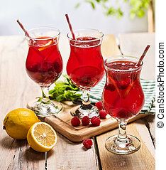 On wooden are ice cold beverage glasses with berries ...