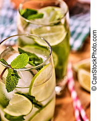 On wooden boards glasses with mohito and lime.