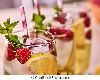 On wooden boards glasses with raspberry mohito and lime.