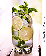 On wooden boards is glass with mohito and lime.