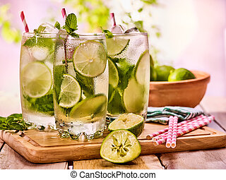 On wooden boards is glasses with mohito and lime.