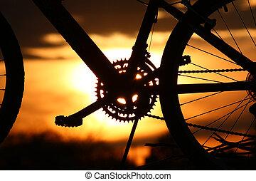 ondergaande zon , op een fiets