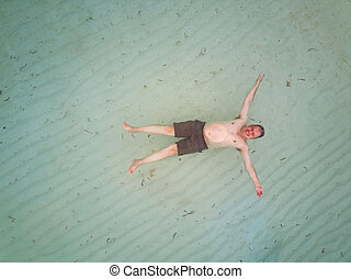 One adult man float on sea water aerial above view
