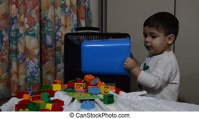One and a half year old baby boy emptying blue bin with lego blocks on the table