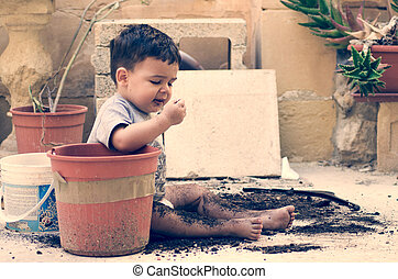 One and a half year old baby boy playing with dirt, planting...