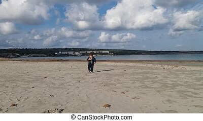 one and a half year old baby boy playing with sea weed balls on the sandy beach with no people, sunny day with blue sky