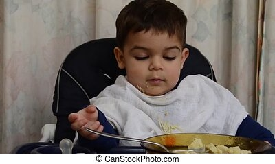 One and a half years old baby boy eating soup with spoon by himself