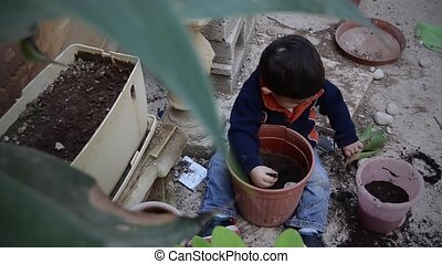 one and a half years old baby boy playing with dirt and planting aloe verde plant