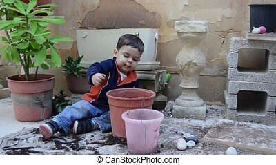 one and a half years old baby boy playing with dirt