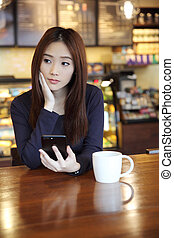 one Asian woman thinking with smartphone