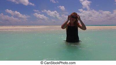 one beautiful young girl standing in bikini sunbathing by the aqua blue sea water on white sand in the sun