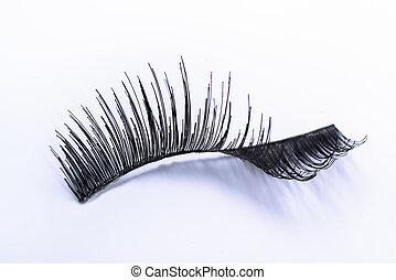 one bent false eyelash on a white background