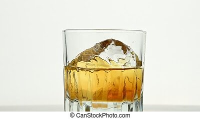 One big ice rock spins in whiskey glass on white