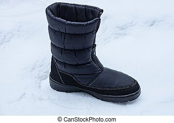 one black boot of matter stands on the white snow outside