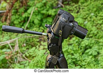 one black camera on a tripod against the background of green vegetation