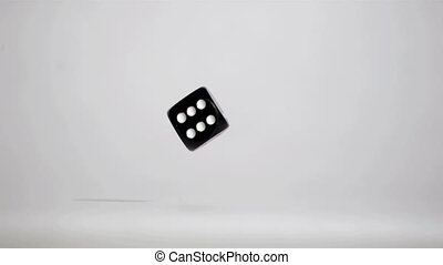 One black dice number six in a super slow motion rebounding