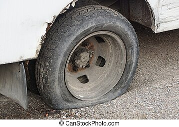 one black flat tire on a white car on gray asphalt