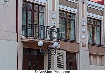 one black iron open balcony and brown windows on the concrete wall of the house on the street with a lantern