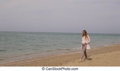 one blonde woman on the beach by the sea