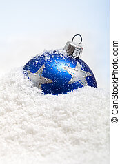 One blue christmas bauble in the snow