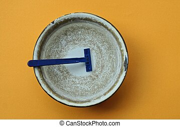 one blue plastic razor in water in a gray metal bowl