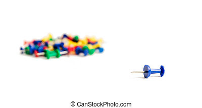 pushpin lies separately from the rest of the heap of the same buttons on a white background