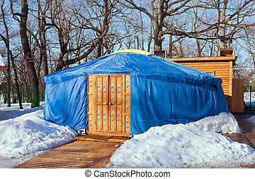 One blue yurt with big closed decorated orange door in the winter park