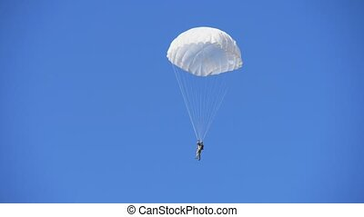 One brave paratrooper swooping down on white round ...