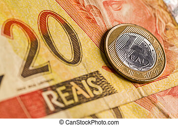 One Brazilian Real coin, over a 20 Real bill. Studio Shot.
