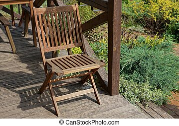 one brown folding chair stands on the open porch of the house