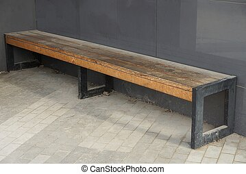one brown wooden bench stands on the sidewalk near the gray metal wall