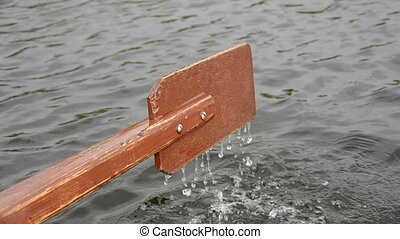 one brown wooden boat oar and water