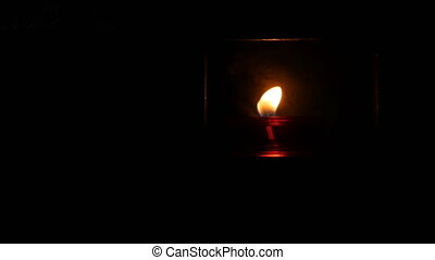 One burning beautiful red round prayer candle in a special ...