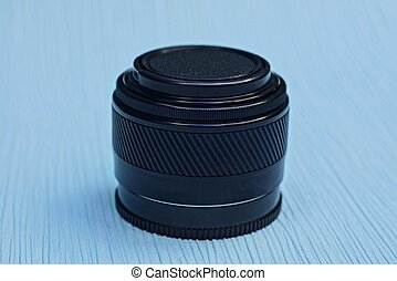camera lens closed by a black cap lies on a blue table