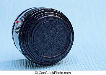 one camera lens closed by a black cap lies