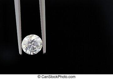 one carat diamond held with tweezers