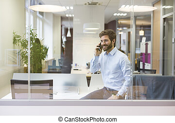 One casual businessman on the mobile phone in open space office