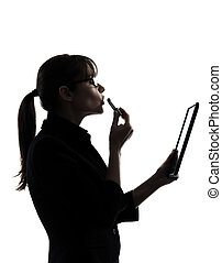 one caucasian business woman computer computing digital tablet applying lipstick in silhouette studio isolated on white background