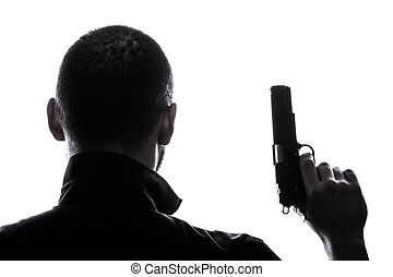 One caucasian man holding gun portrait silhouette in studio...